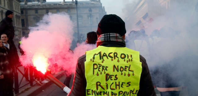"A demonstrator wearing a yellow vests reading ""Macron, Santa Claus for the rich, enemy of the French people"" takes part to a demonstration called by the CGT (General Working Confederation) union, Tuesday, Feb. 5, 2019 in Paris. Workers, public servants, and retired people were invited to march during a strike called by the CGT (General Confederation of Labor) union."
