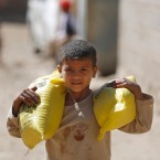 A displaced boy who fled Saada province, northwest of Sanaa with his family, carries relief supplies to his family during a food distribution by Yemeni volunteers in Sanaa, Yemen, Thursday, Dec. 17, 2015.
