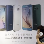 A visitor uses his smartphone in front of an advertisement of Samsung Electronics' Galaxy S6 and S6 Edge smartphone at a Samsung Electronics shop in Seoul, South Korea, in 2015.