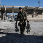 A member of U.S.-backed Syrian Democratic Forces (SDF) carries explosives at a stadium that that was the site of Islamic State fighters' last stand in the city of Raqqa, Syria, Wednesday, Oct. 18, 2017.