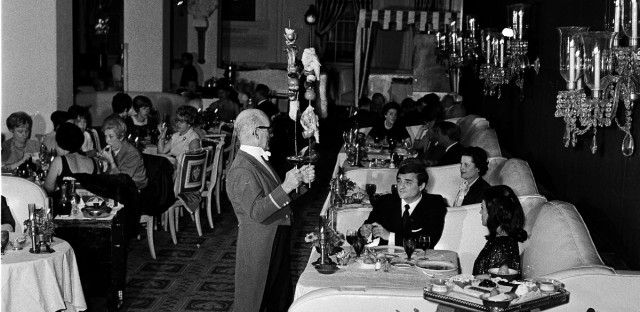 When the late Ernie Byfield opened the Pump Room in Chicago in 1938, he thought of the restaurant as a stage. More than 28 years later it still ranks at the top of Chicago's restaurants, and still carries on Byfield's tradition of dramatic effects. Here waiter Lee Scott, in tail coat, serves flaming lamb chops and chicken on brochette June 29, 1967 to recording artist Joni James and her husband, Anthony Acquaviva, of Beverly Hills, Calif., in Booth one reserved for celebrities.