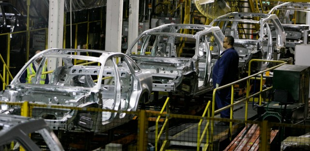 A Ford Motor Company employee watches chassis for the 2008 Ford Taurus, 2008 Ford Taurus X, and Mercury Sable roll by on the assembly line, Friday, June 22, 2007 at the Chicago Assembly Plant.