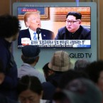 People watch a TV screen showing file footage of U.S. President Donald Trump, left, and North Korean leader Kim Jong Un during a news program at the Seoul Railway Station in Seoul, South Korea, Wednesday, May 16, 2018.