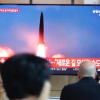 """People watch a TV showing a file image of a North Korea's missile launch during a news program at the Seoul Railway Station in Seoul, South Korea, Tuesday, Aug. 6, 2019. North Korea on Tuesday continued to ramp up its weapons demonstrations by firing unidentified projectiles twice into the sea while lashing out at the United States and South Korea for continuing their joint military exercises that the North says could derail fragile nuclear diplomacy. The sign reads """"North Korea could seek a new road."""""""