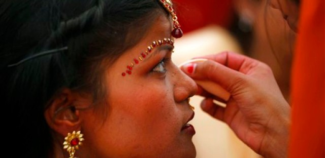 A family member applies makeup on an Indian bride before a ritual at a mass marriage in Allahabad, India.