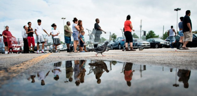 People wait in line to buy groceries at a Food Town during the aftermath of Hurricane Harvey in Houston, Texas. More than 30,000 people are currently in more than 230 shelters, the Federal Emergency Management Agency says.