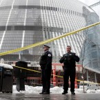 Chicago police officers remain on the scene outside the James R. Thompson Center after off-duty Police Cmdr. Paul Bauer was shot several times as he went to assist tactical officers pursuing a fleeing suspect near the center on Tuesday, Feb. 13, 2018, in Chicago. (AP Photo/Charles Rex Arbogast)