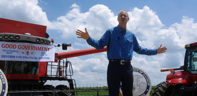 Illinois Gov. Bruce Rauner speaks to farmers and local area residents about the need for term limits and redistricting reform while visiting the Garry Niemeyer corn and soybean farm Tuesday, July 26, 2016, in Auburn, Ill.