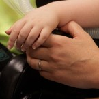 A woman listens as she holds hands with her daughter at a meeting with the Illinois Department of Healthcare and Family Services on Wednesday, July 11, 2012, in Chicago.