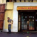 A homeless man stands in front of a closed down fast food restaurant in the colonial district of Old San Juan, Puerto Rico, Sunday, Aug. 2, 2015. As Puerto Rico's economy continues to decline a list of cost-cutting measures proposed by a group of hedge funds that holds $5.2 billion of Puerto Rico's debt has riled islanders: laying off teachers; cutting Medicaid benefits; and reducing subsidies to the main public university.