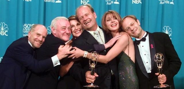 """Cast members of """"Frasier,"""" winner of the Emmy for Outstanding Comedy Series, have a group hug backstage at the 50th Annual Primetime Emmy Awards at the Shrine Auditorium in Los Angeles, Sunday, Sept. 13, 1998. From left are Dan Butler, John Mahoney, Peri Gilpin, Kelsey Grammer, Jane Leeves and David Hyde Pierce. Grammer and Pierce also won Emmys. (AP Photo/Reed Saxon)"""