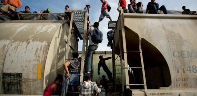 Central American migrants climb on a northbound train during their journey toward the U.S.-Mexico border, in Ixtepec, Mexico.