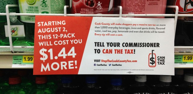 A sign sponsored by opponents of the new Cook County tax on sweetened beverages is posted in the soda aisle of Tischler Finer Foods in Brookfield, Ill. on Aug. 22, 2017.