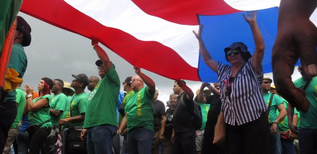 People carry a large Puerto Rican flag