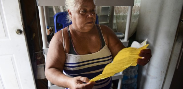 In this June 13, 2018 photo, Carmen Lidia Torres Mercado reviews a document delivered by FEMA contractors after installing a roof awning on her residence located in the Barriada Figueroa neighborhood of San Juan, Puerto Rico. The 60-year-old retiree says she has no money to fix the roof on her own and doesn't have the documents proving home ownership she would need to qualify for assistance from FEMA.