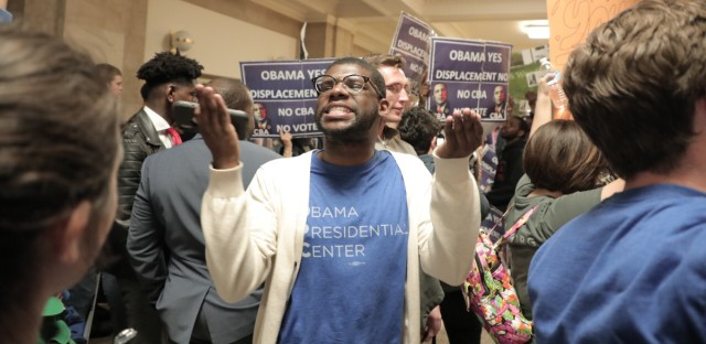 """Obama Foundation employee Jaylin D. McClinton encourages a chant of """"OPC"""" (Obama Presidential Center) against an opposing chant of """"CBA"""" (Community Benefits Agreement) before the Chicago Plan Commission's Thursday meeting."""