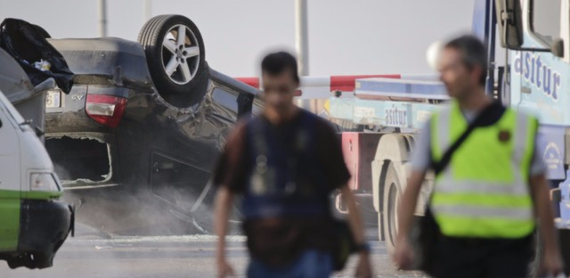 Police officers walk near an overturned car in Cambrils on Friday. (Emilio Morenatti/AP)