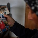 Dahouk al-Omar, 68, an unregistered Syrian refugee in Lebanon who hopes she can join her son in Chicago, shows old pictures of her family members on Saturday, June 30, 2018.