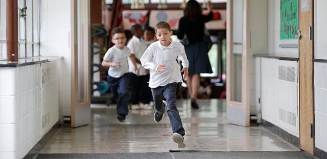 Students run to go outside at the start of a recess between classes on June 7, 2016.