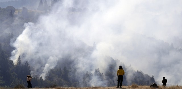 A firefighter, center, and two onlookers watch a smoldering wildfire from a hilltop, on Sunday, in Oakville, Calif.