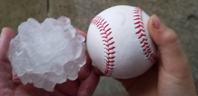 This photo provided by Tim Creedon shows his baseball and a hailstone that fell in the backyard of Creedon's home in Ottawa, Ill., Tuesday, Feb. 28, 2017. Illinois Gov. Bruce Rauner has activated the state's emergency operations center as local officials reported damage from tornados spawned by a late-winter storm system.