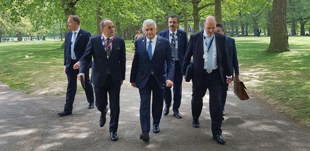 Turkey's Prime Minister Binali Yildirim, centre, walks through central London's Green Park, during a break at the 2017 Somalia Conference in London, Thursday, May 11, 2017. The Somalia Conference was aimed at improving stability and prosperity in Somalia and boosting the humanitarian response to the drought. (Prime Minister's Press Service, Pool Photo via AP)