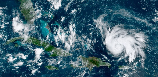 This GOES-16 satellite image taken Thursday, Aug. 29, 2019, at 14:20 UTC and provided by National Oceanic and Atmospheric Administration (NOAA), shows Hurricane Dorian, right, moving over open waters of the Atlantic Ocean. The U.S. National Hurricane Center said Dorian was expected to grow into a potentially devastating Category 3 hurricane before hitting the U.S. mainland late Sunday or early Monday somewhere between the Florida Keys and southern Georgia.