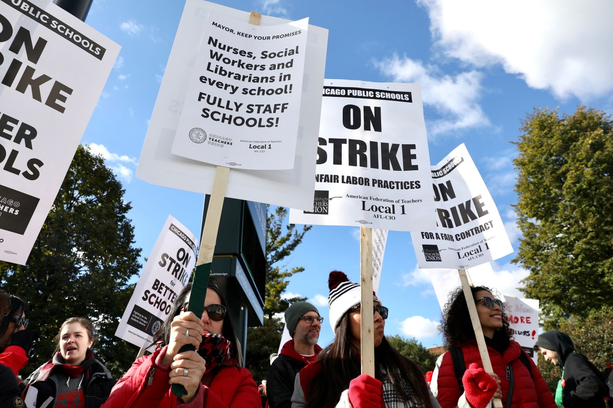 Teachers hold up signs that say 'Nurses, Social Woekrs and Librarians in every school!'