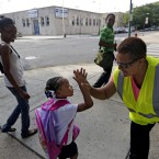 In this Aug. 26, 2013 file photo safety guard Renee Green high-fives Demari Hill, 5, as she heads to Gresham Elementary School with her parents Destiny and Anthony Hill on her first day of kindergarten classes in Chicago