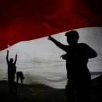 Supporters of the losing presidential candidate walk under a giant Indonesia national flag in Jakarta, Indonesia. Wednesday, May 22, 2019. Indonesian President Joko Widodo said authorities have the volatile situation in the country's capital under control after a number of people died Wednesday in riots by supporters of his losing rival in last month's presidential election.