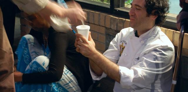 Artist/veteran Aaron Hughes serving tea to artist Michael Rakowitz