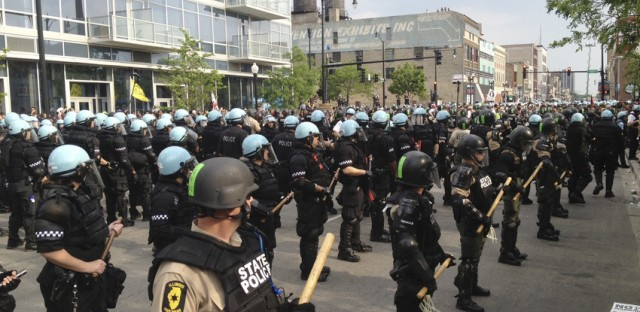 Illinois State police and Chicago police stand guard on Michigan Avenue during a NATO-related protest march Sunday.