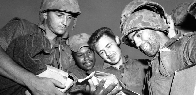 Four tired, bearded and grimy U.S. Marines just off the fighting line on western Korean front, read good news in an official handout that armistice to end war was about to be signed at Panmunjom on July 26, 1953. Identifiable at right is PFC Thomas W. O'Connell of Hammond, Wis.