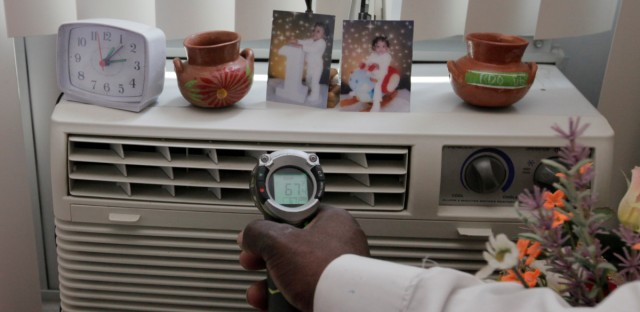 A man checks an air conditioning unit in Chicago in July of 2012. On Friday, a Cook County judge ordered air conditioning units be installed at a building in every unit of a South Side seniors building.