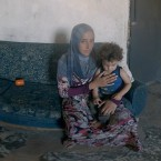A Syrian woman and her child sit in their refugee living space in Lebanon. They are featured in Four Walls, a virtual reality presentation by the International Rescue Committee.