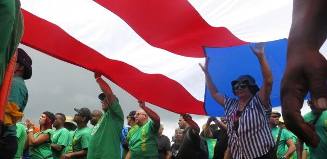 People carry a large Puerto Rican flag as they protest looming austerity measures amid an economic crisis and demand an audit on the island's debt to identify those responsible, in San Juan, Puerto Rico, Monday, May 1, 2017. Puerto Rico is preparing to cut public employee benefits, increase tax revenue, hike water rates and privatize government operations, among other things.