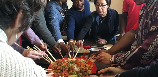 Alex Wong and his friends place their chopsticks into his homemade Yusheng as they get ready to toss it in the air.