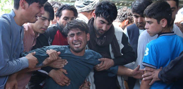 Relatives grieve near the coffins of victims of the Dubai City wedding hall bombing during a mass funeral in Kabul, Afghanistan, Sunday, Aug.18, 2019. The deadly bombing at the wedding in Afghanistan's capital late Saturday that killed dozens of people was a stark reminder that the war-weary country faces daily threats not only from the long-established Taliban but also from a brutal local affiliate of the Islamic State group, which claimed responsibility for the attack.