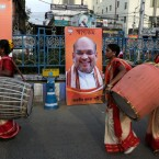 Indian drummers perform as they walk past portraits of India's ruling Bharatiya Janata Party (BJP) president Amit Shah, center and Prime Minister Narendra Modi, left during an election rally in Kolkata, India, Tuesday, May 14, 2019. India's staggered national elections are underway with the last day of voting set for May 19. Results are expected four days later.
