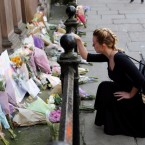 A woman lays flowers for the victims of the Manchester Arena attack