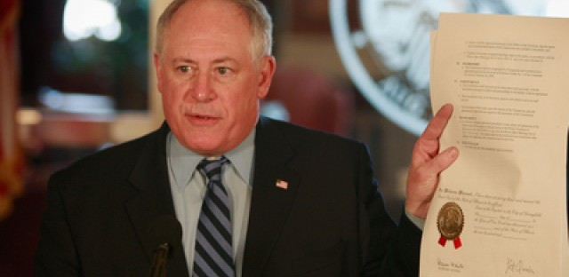 Gov. Pat Quinn holds a signed executive order during a press conference in January.