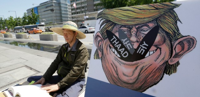 A South Korean protester sits next to a poster with an illustration of U.S. President Donald Trump to oppose a plan to deploy an advanced U.S. missile defense system called Terminal High-Altitude Area Defense, or THAAD, near the U.S. Embassy in Seoul Monday, June 5, 2017. South Korea's presidential office says a senior defense official has been suspended for deliberately failing to report the arrival of several more launchers for a contentious U.S. missile defense system meant to deal with North Korean threats.