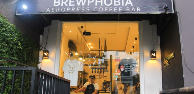 Mirza Luqman Effendy, founder of the Brewphobia coffee shop in South Jakarta, is seen through the window in his shop.