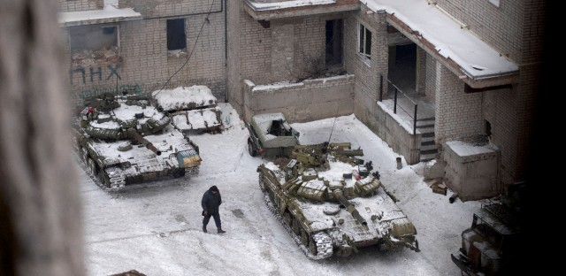 A Ukrainian serviceman walks past Ukrainian tanks in Avdiivka, eastern Ukraine, Thursday, Feb. 2, 2017. Two Ukrainian soldiers have been killed in the country's industrial east as both government forces and rebels reported shelling on their positions overnight, Ukraine's government said early Thursday.