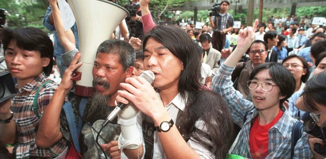 Pro-democracy activist Leung Kwak Hung, holding a microphone, is surrounded by supporters, Wednesday, Nov. 26, 1997, during a demonstration outside the Hong Kong Legislative Council during legislative session against being barred from entering the bulding to protest against what he considered social injustices.