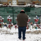 A man prays at a makeshift memorial on Feb. 17, 2019, in Aurora, Ill., near Henry Pratt Co. manufacturing company where several were killed on Friday. Authorities say an initial background check five years ago failed to flag an out-of-state felony conviction that would have prevented a man from buying the gun he used in the mass shooting in Aurora. (AP Photo/Nam Y. Huh)
