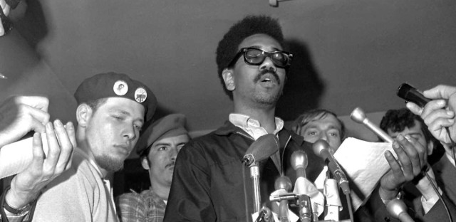 """** FILE ** Bobby Rush, deputy defense minister of the Illinois Black Panther party, reads a statement June 4, 1969, during a news conference following an early morning raid on the Chicago Panther headquarters by FBI agents, who arrested eight persons. Rush called the raid """"...a trick ..to attack the party."""" At left, Cha Cha Jimenez, chairman of the Young Lord, a Chicago-area Puerto Rican group."""