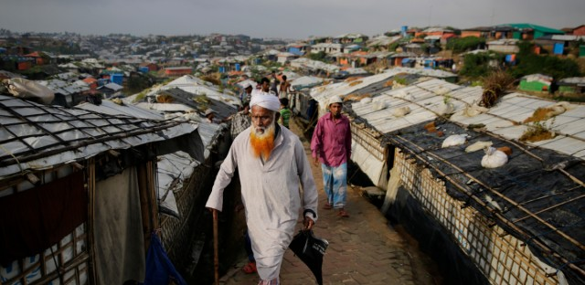 In this Wednesday, Aug. 22, 2018, file photo, an elderly Rohingya refugee walks toward a makeshift mosque to offer Eid al-Adha prayers at Kutupalong refugee camp, Bangladesh. Hundreds of thousands of Rohingya refugees are celebrating Eid al-Adha in sprawling Bangladeshi camps where they have been living amid uncertainty over their future after they fled Myanmar to escape violence and a massive crackdown.