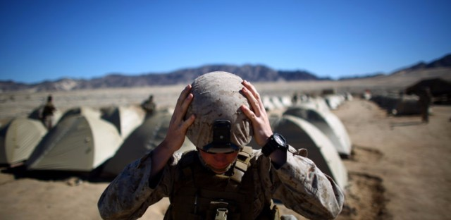 Sgt. Kelly Brown adjusts her helmet before a weapons check last year at the Marine Base at Twentynine Palms in the Mojave Desert, Calif. The Marine Corps set up a months-long training exercise to determine whether women could serve in ground combat jobs like artillery, armor and infantry. Women are now eligible to apply for these positions.