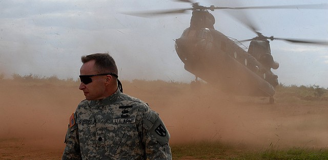 Lt. Col. Michael Cortez, Commander, 21st Theater Sustainment Command Special Troops Battalion, braces for the down draft from a landing CH-47 Chinook, Kitgum, Uganda, Oct. 16, 2009.
